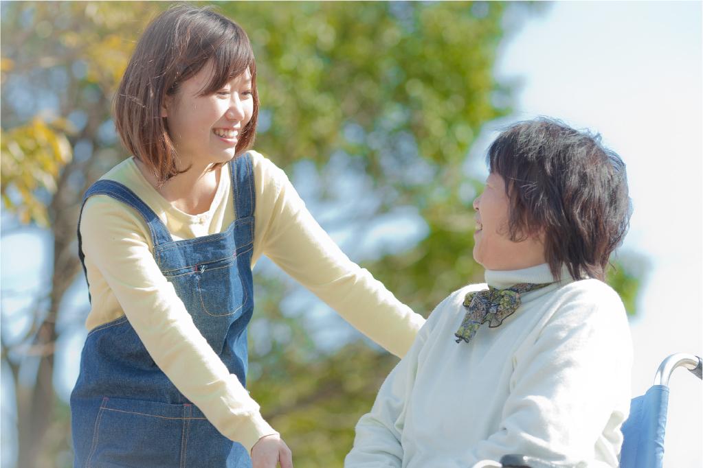向かい合う女性と車椅子に乗った女性